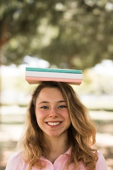 Femme étudiante avec des livres sur la tête