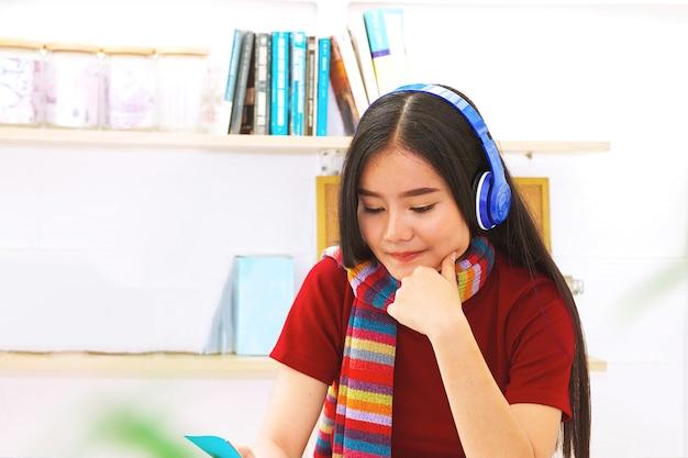 Une femme étudie un livre en écoutant un casque