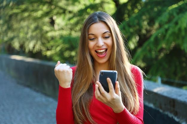 Femme euphorique regardant son téléphone et montrant le geste du gagnant