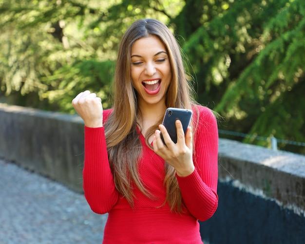 Femme euphorique regardant son téléphone en plein air