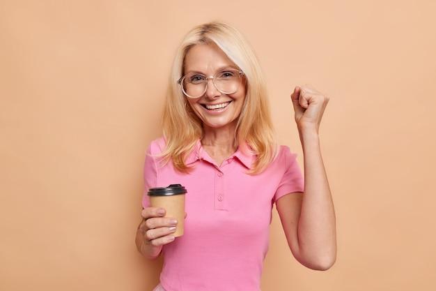 Une femme européenne d'âge moyen aux cheveux blonds et ravie, serre le poing, célèbre le succès, boit du café à emporter, porte de grandes lunettes optiques, un t-shirt rose décontracté isolé sur un mur beige