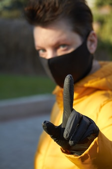 Femme européenne d'âge moyen dans un masque de protection noir fait un geste d'avertissement pendant l'épidémie de coronavirus covid-19. femme malade portant une protection pendant la pandémie.