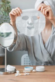 Femme européenne assise devant le miroir et appliquant un masque hydratant en tissu blanc sur elle