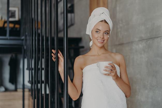 Femme européenne attrayante en bonne santé avec une expression pensive sourit doucement