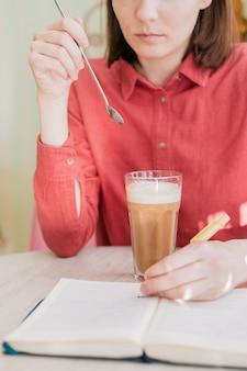 Une femme européenne boit du café dans une tasse de café dans un café, une femme blanche boit un café au lait ou un cappuccino dans un restaurant pour le petit-déjeuner ou le déjeuner, savoure le goût du café et socialise avec des amis