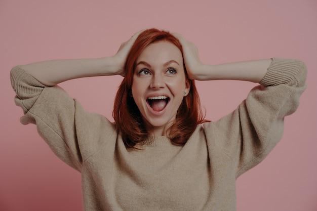 Femme européenne choquée surprise tenant la tête dans les mains et regardant à l'envers avec une expression excitée et une bouche ouverte, entendant parler de gros prix de vente, debout en studio isolé sur fond rose