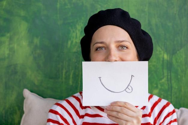 Femme européenne dans un béret noir tenant un autocollant avec un visage souriant sourire peint comme un masque