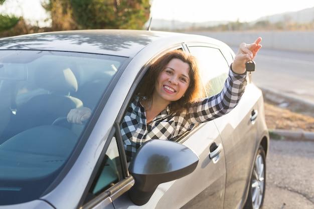 Femme européenne derrière la roue de voiture montrant la clé de voiture