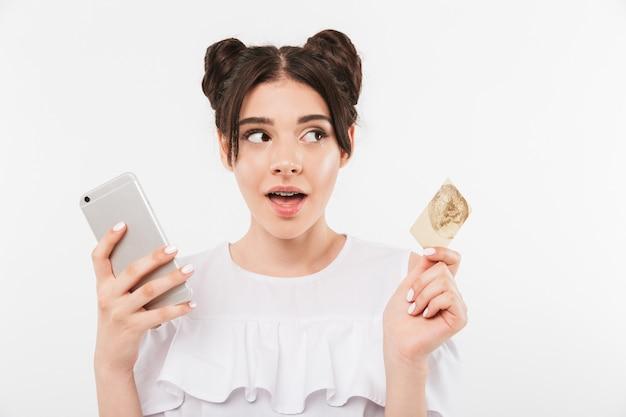 Femme européenne avec double chignon coiffure et appareil dentaire à la recherche de côté tout en utilisant un smartphone et une carte de crédit pour faire du shopping en ligne, isolé sur un mur blanc