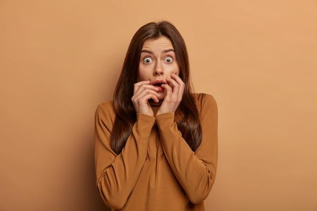 Une femme européenne effrayée halète d'émerveillement, regarde avec des yeux écarquillés, garde les mains sur les joues, tremble de peur, porte un pull marron décontracté, inquiète et peu sûre de lui