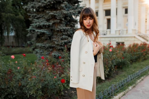Femme européenne élégante avec des cheveux ondulés posant dans la rue. look élégant.