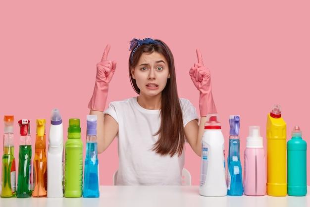 Une femme européenne frustrée perplexe serre les dents et regarde avec frustration, vêtue d'un tshirt blanc décontracté et d'un bandeau