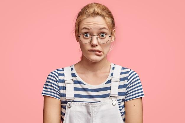 Une femme européenne inquiète mord la lèvre inférieure, regarde avec une expression perplexe, porte une tenue à la mode, se tient contre le mur rose