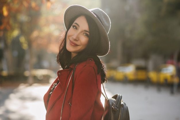 Femme européenne inspirée en veste rouge décontractée à la recherche d'appareil photo sur le mur de la nature