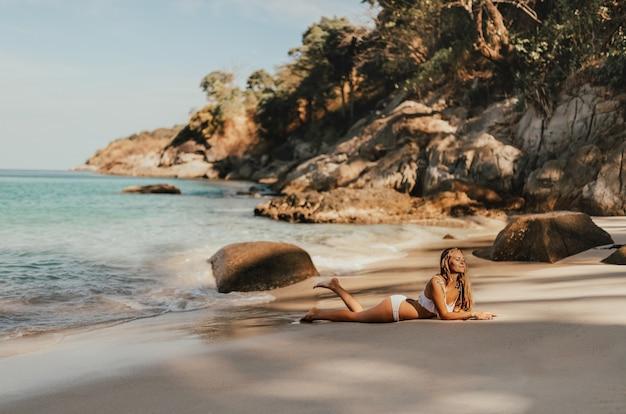 Femme européenne en maillot de bain bikini blanc posant sur la plage