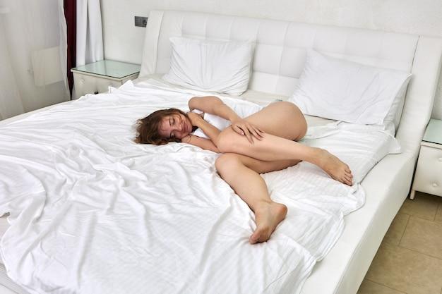 Femme européenne mince de 29 ans allongée dans son lit pendant qu'elle dort dans la chambre.