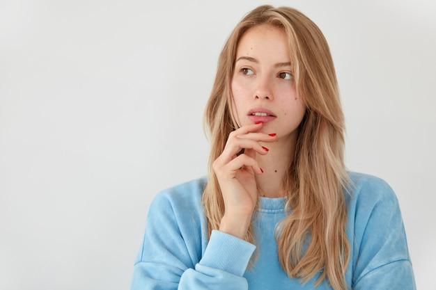 Femme européenne pensive tient la main sur le menton, regarde de côté avec une expression rêveuse, contemple quelque chose, habillé avec désinvolture