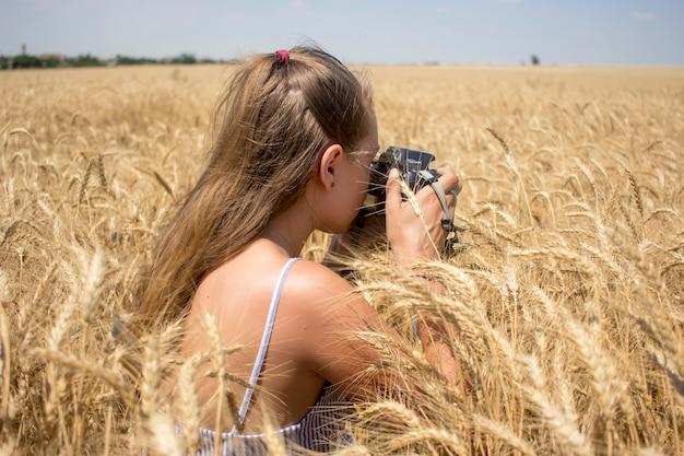 Une femme européenne photographie un champ de blé