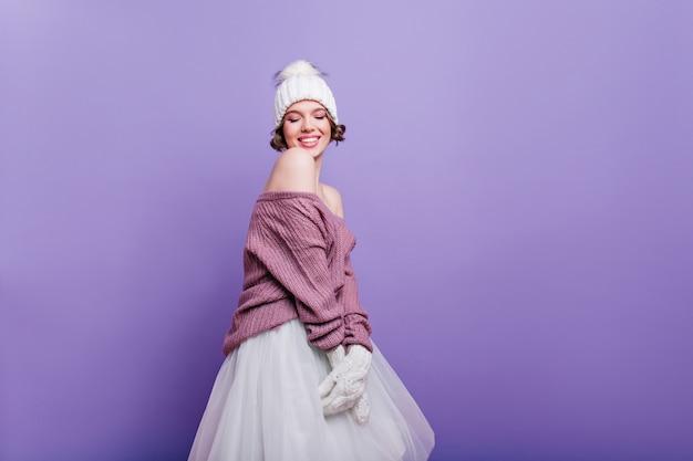 Femme européenne raffinée en chapeau blanc et jupe posant avec une expression de visage inspirée. fille aux cheveux courts à la mode en pull isolé sur mur violet.