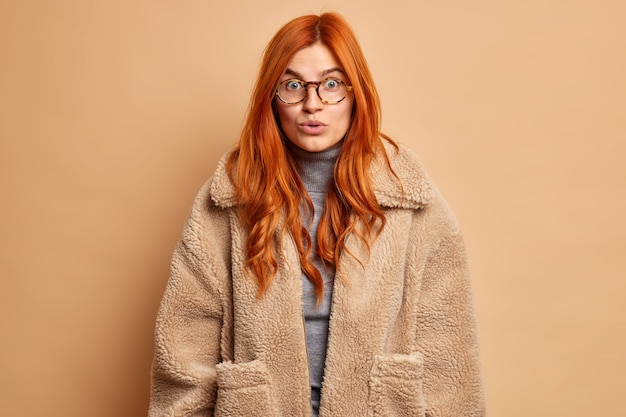 Une femme européenne rousse étonnée entend des rumeurs incroyables ou un secret impressionné par quelque chose porte des lunettes transparentes et un manteau brun fourrure.