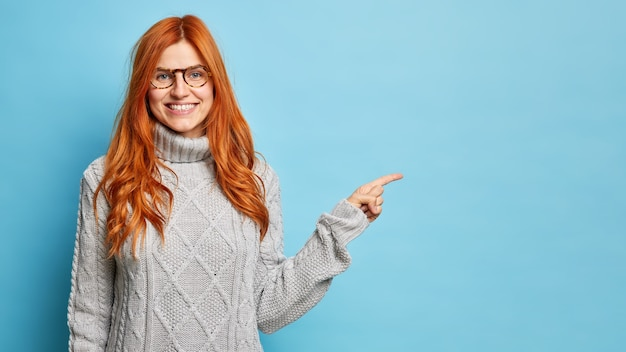 Une femme européenne rousse joyeuse à lunettes sourit largement et pointe du doigt sur l'espace de copie donne la direction au meilleur magasin porte un pull d'hiver chaud.
