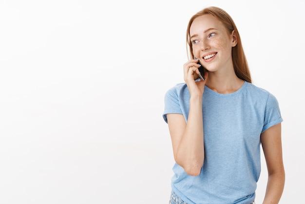 Femme européenne rousse ordinaire détendue insouciante avec des taches de rousseur en t-shirt bleu tournant à gauche tout en tenant le téléphone près de l'oreille et en parlant