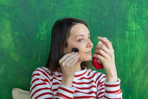 Une femme européenne se maquille une femme caucasienne met de la poudre sur son visage