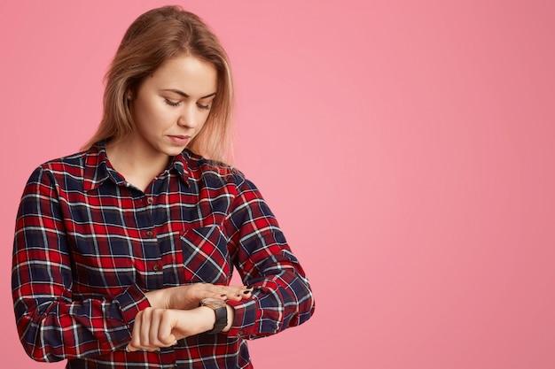 Une femme européenne sérieuse se dépêche de se rencontrer, regarde la montre, vérifie l'heure.