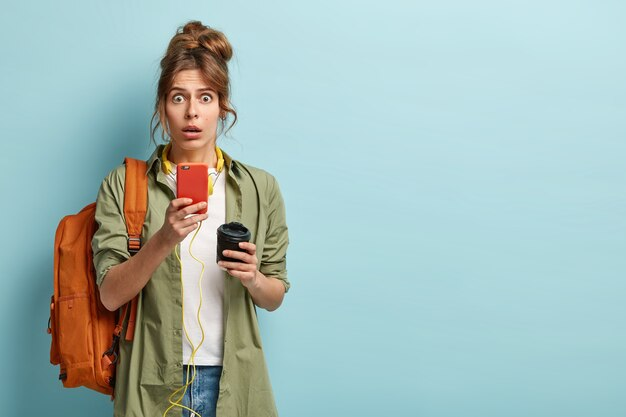 Une femme européenne surprise envoie un message texte sur son téléphone portable et écoute de la musique, s'est largement ouverte