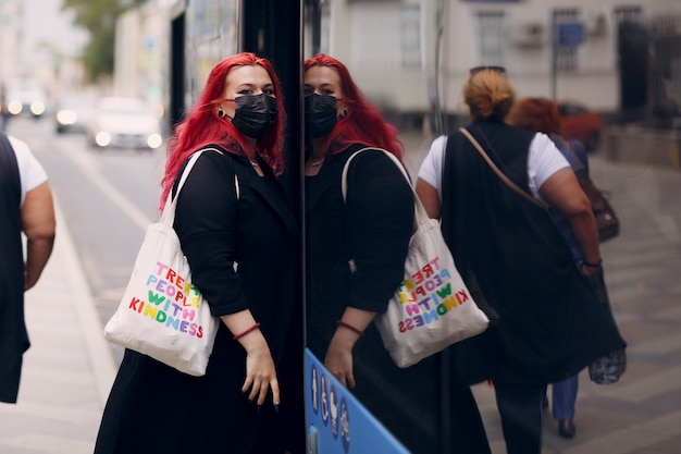 Une femme européenne de taille plus monte dans le bus avec un masque facial jeune fille positive aux cheveux roses rouges