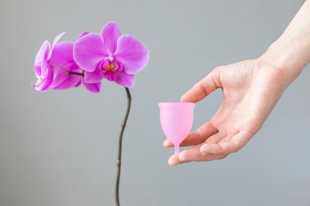 Une femme européenne tient une coupe menstruelle rose en silicone dans ses mains