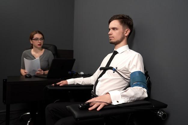 Femme examinant l'homme avec détecteur de mensonge.