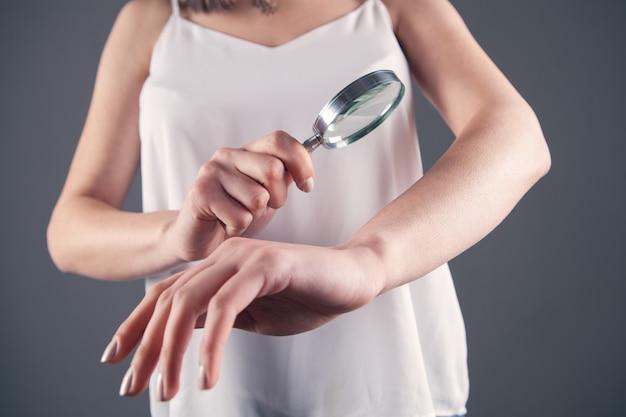 La femme examine sa main avec une loupe