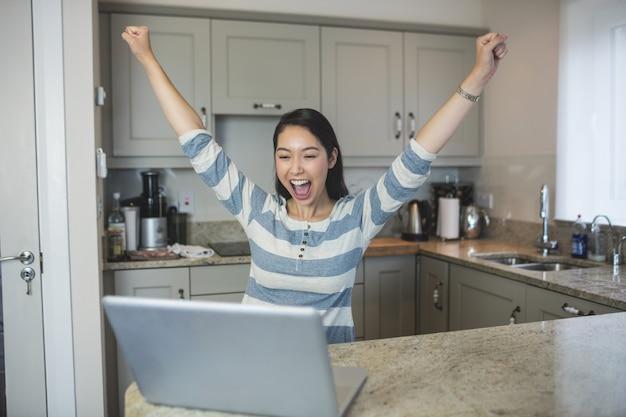 Femme excitée à l'aide d'un ordinateur portable dans la cuisine