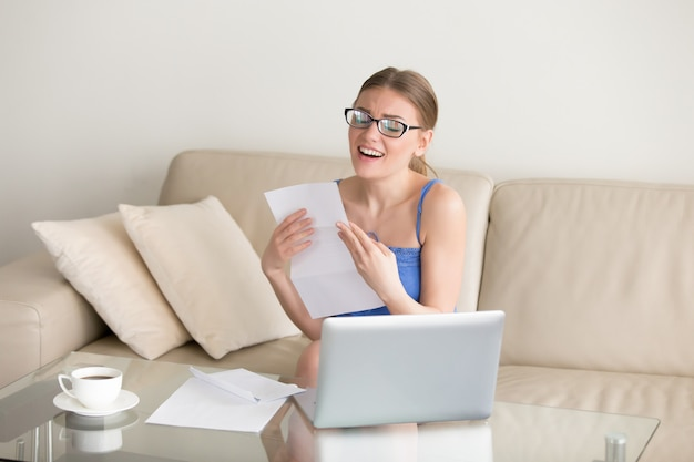 Femme excitée bénéficiant d'une lettre de bons résultats, ayant obtenu un emploi, réussi un examen