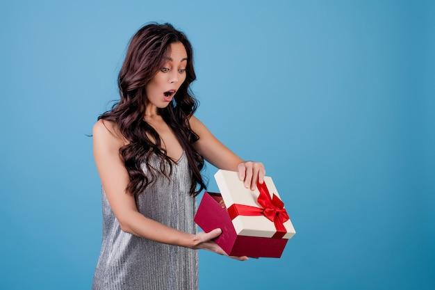 Femme excitée avec une boîte cadeau avec ruban rouge portant une robe isolée sur bleu