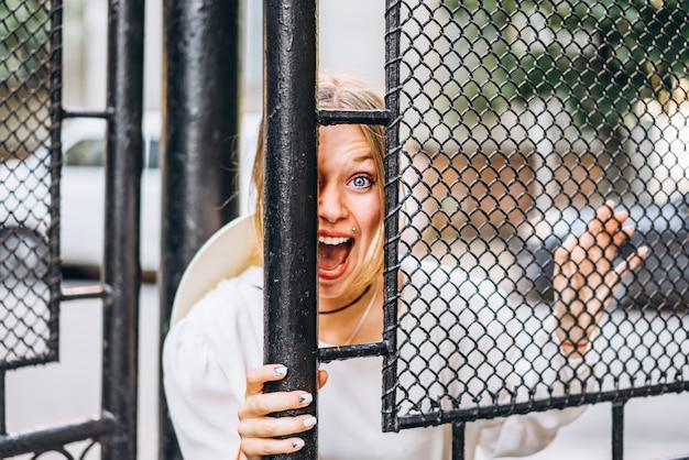 Femme excitée dans la rue derrière les portes