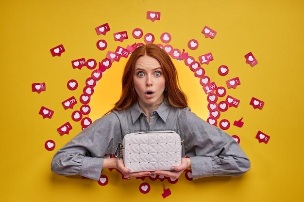 Femme excitée drôle tenant un sac à main, isolé sur un mur jaune