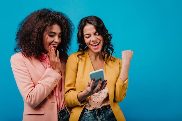 Femme excitée faisant selfie avec un ami
