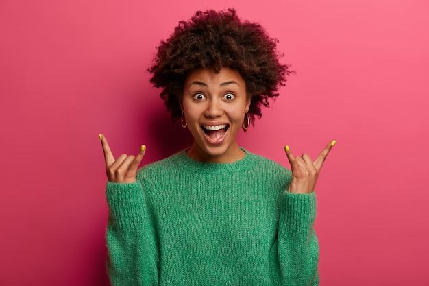 Une femme excitée et frisée énergisée positive fait signe de rock, passe du temps libre au concert du groupe préféré, s'exclame joyeusement en entendant une chanson géniale, vêtue d'un pull vert, pose sur un mur lumineux rose