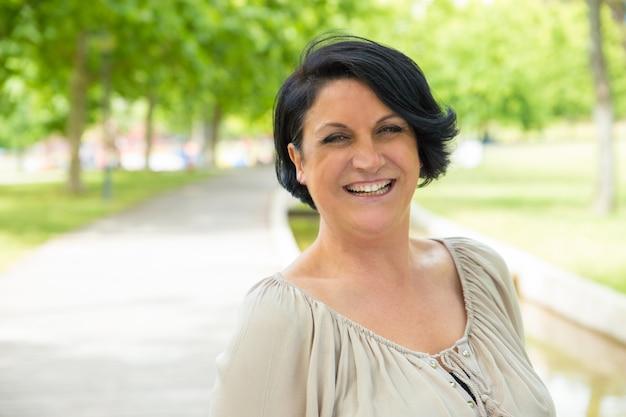 Femme excitée joyeuse qui marche dans le parc