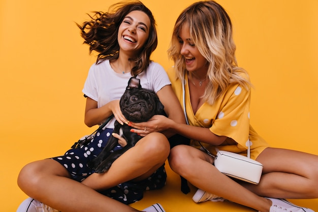 Femme excitée en jupe noire posant avec son chiot. sœurs raffinées assis sur jaune vif tout en jouant avec le bouledogue français.