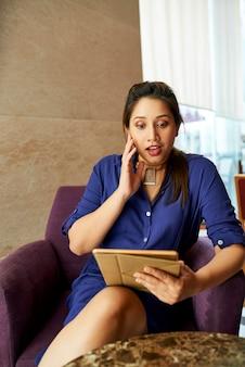 Femme excitée lisant des nouvelles passionnantes