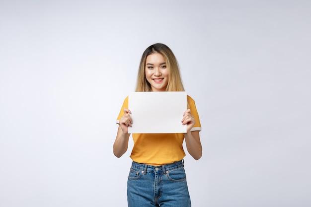Femme excitée montrant le signe de la carte de papier vierge vide avec espace copie de texte