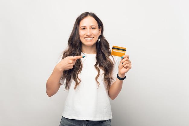Une femme excitée pointe du doigt la carte qu'elle tient sur fond blanc.