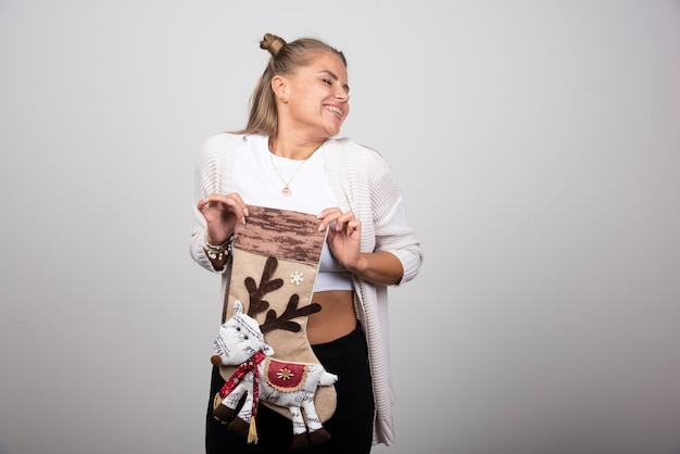 Femme excitée posant avec des bas de noël sur fond gris.