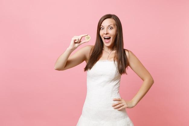 Femme excitée en robe blanche tenant une pièce de métal bitcoin de future devise de couleur dorée