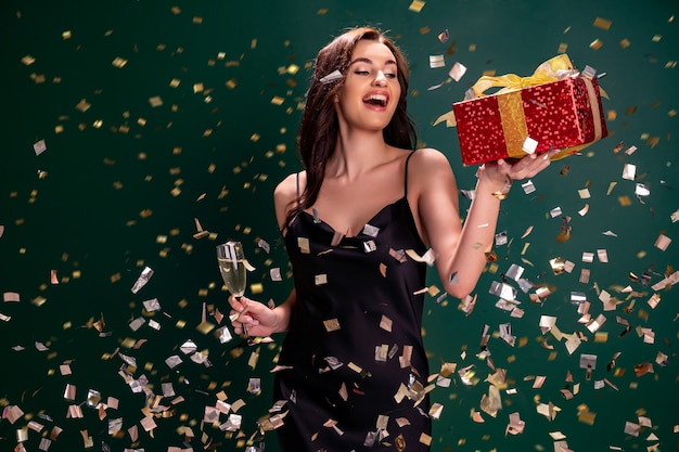 Une femme excitée en robe noire tient la boîte rouge cadeau et un verre de concept de vacances de fête au champagne