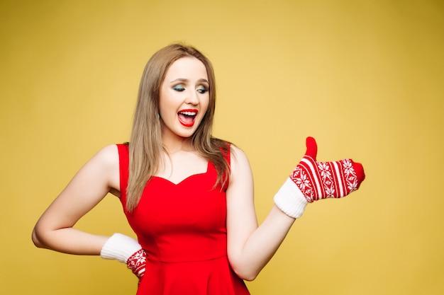 Femme excitée en robe rouge pointant vers un espace vide en mitaine