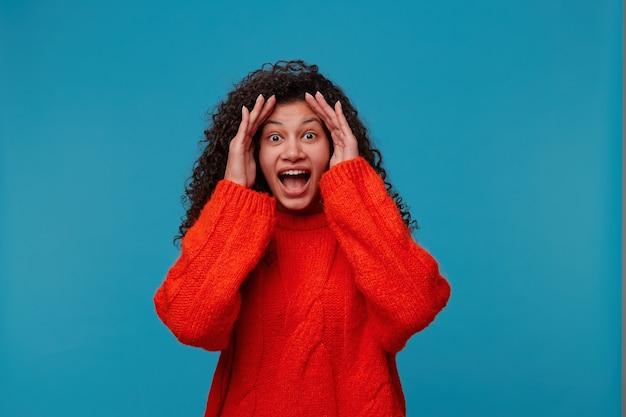 Une femme excitée surprise ne croit pas à son succès, garde les mains sur la tête, regarde devant